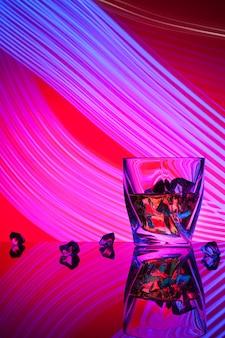 Виски коктеиля стекло с льдом частей световых эффектов концепции партии фиолетовых на красном цвете.
