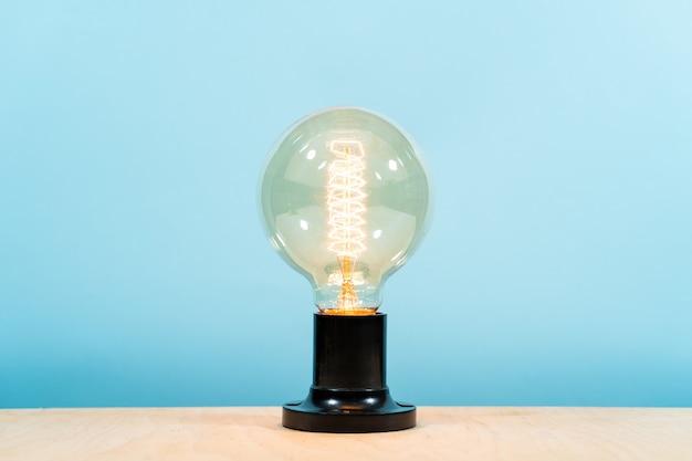 エジソンの電気ランプ、青色の背景に。独創的なアイデア。ロフトスタイル、広告スペース。安全な照明、デザイン。