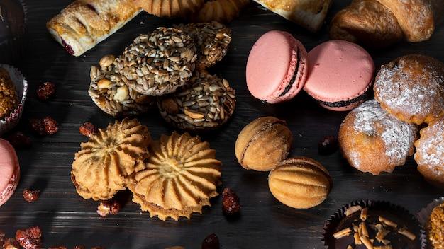 Печенье, кексы, круассаны, макароны, выпечки сладости прорастают стиль на деревянном столе. вкусный набор для кофе или чая.