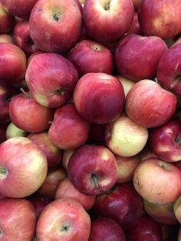 ストア内の赤い甘いリンゴの背景。ベジタリアン料理、健康的なビタミン。