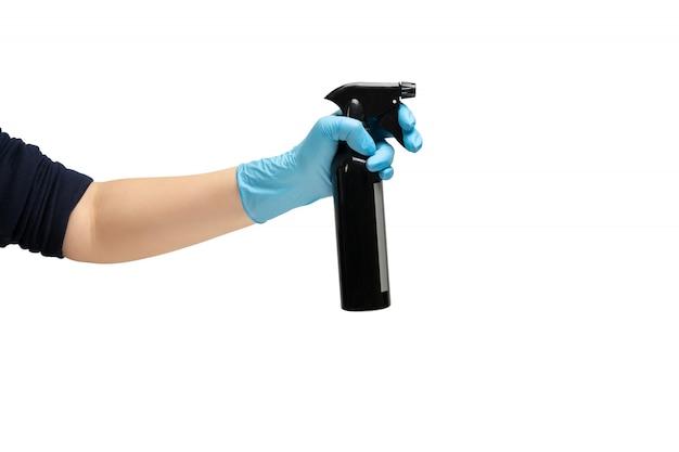 Женская рука в защитной резиновой медицинской перчатке синего цвета, держит черную металлическую бутылочку с антисептическим дозатором, для борьбы с бактериями.