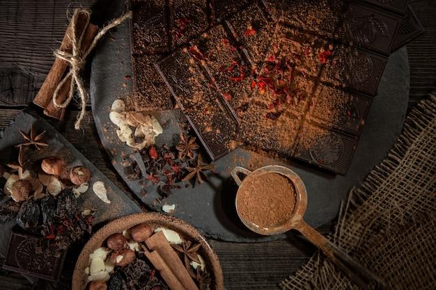 オデッサ、ウクライナ。ミレニアムチョコレートバーロスティック、チョコレート、ココア、スパイス、スパイスシナモン、赤唐辛子、暗い背景に。
