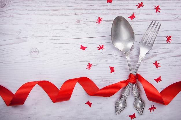 ビンテージスプーンとフォーク赤い木製のテーブルの上のバレンタインデーのための赤いテープ、天使と蝶。