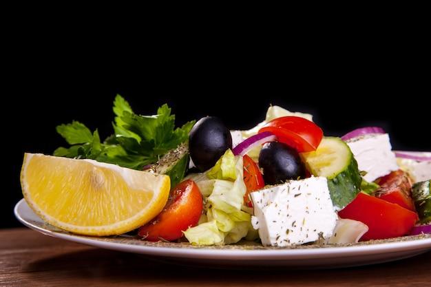 Салат с сыром фета, маслинами, листьями салата, помидорами, огурцами, лимоном на черном фоне.