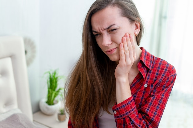Молодая женщина страдает и испытывает сильную ноющую зубную боль. кариес и чувствительность