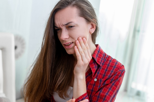 Молодая женщина страдает и испытывает сильную ноющую зубную боль. разрушение и чувствительность зубов. заболевания десен