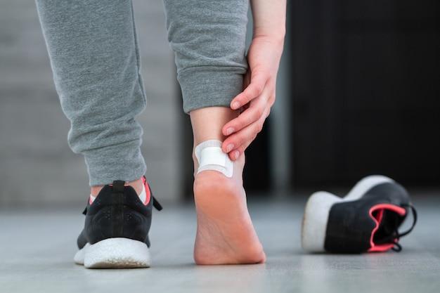 新しい靴を履いている間にカルスから医療用絆創膏を使用する