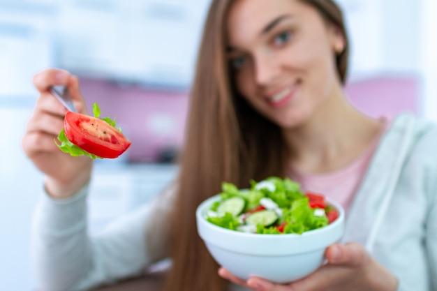 Портрет молодой счастливой здоровой женщины, едят салат из свежих овощей в домашних условиях. чистая и контролируемая пища