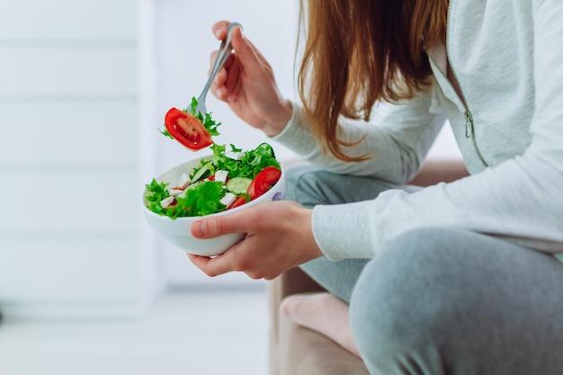 Здоровая женщина в спортивной одежде, держа миску салат из свежих овощей в домашних условиях
