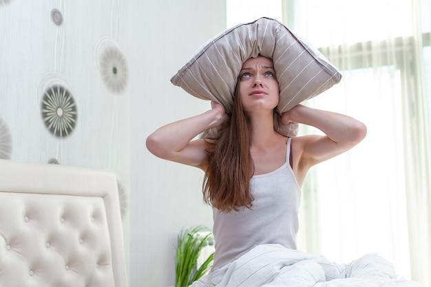 Грустная женщина страдает и встревожена шумными соседями и прикрывает уши подушкой, пытаясь заснуть дома рано утром