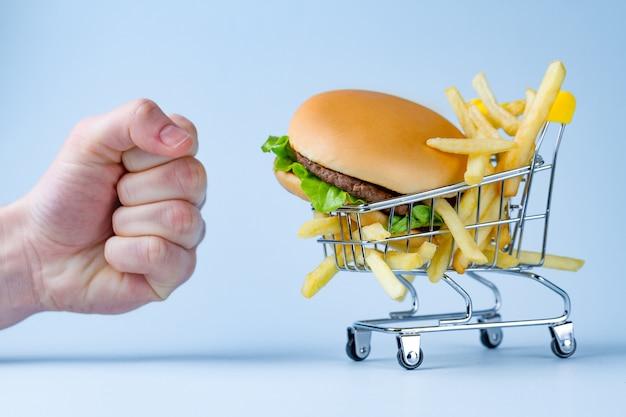 食べ物と食事のコンセプト。フライドポテトとスナックのハンバーガー。太りすぎと肥満との戦い。ジャンク品、不健康な食べ物の拒否