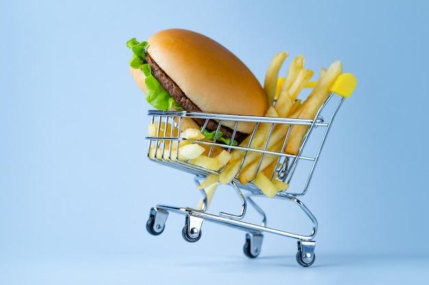 食品のコンセプト。フライドポテトとスナックのハンバーガー。ファーストフード中毒。