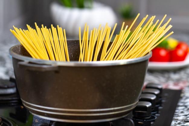 自宅のキッチンで鍋でスパゲッティを調理