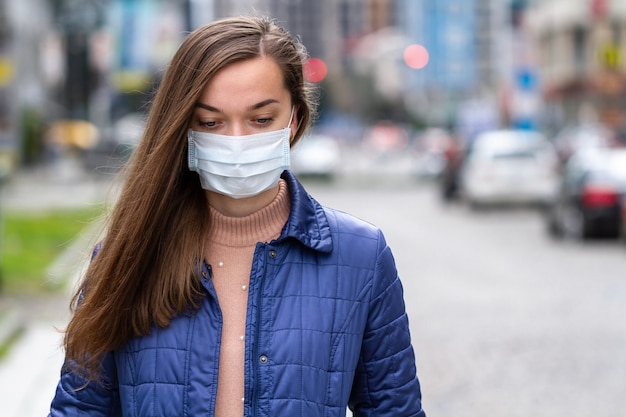 路上の医療マスクの女性。都市部でのウイルス、感染、排気、産業排出物に対する保護。大気汚染と都市の流行