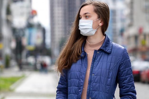 路上で医療マスクを着ている女性。都市部でのウイルス、感染、排気、産業排出物に対する保護。大気汚染と都市の流行
