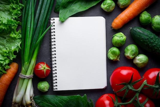 Пустая книга рецептов и различные спелые овощи для приготовления свежего салата и здоровых блюд. правильное питание, чистая сбалансированная еда. план диеты и контроль продуктов питания. контрольный дневник