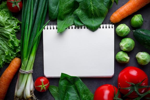 空白のレシピ本と新鮮な野菜の料理の材料。きれいな食べ物とバランスの取れた食事