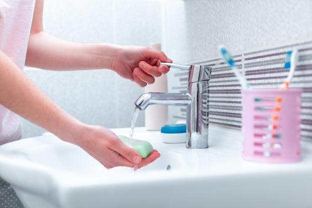 浴室の水で蛇口の下で石鹸で手を洗う。衛生概念とハンドケア。ウイルスと細菌に対する保護と予防