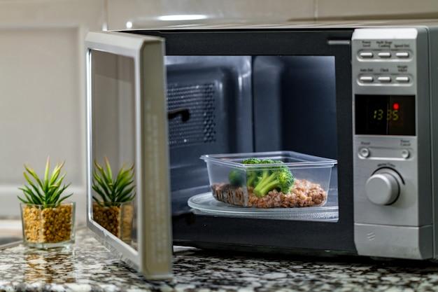 電子レンジを使用して食品を加熱します。電子レンジでブロッコリーとそばでプラスチック容器を加熱