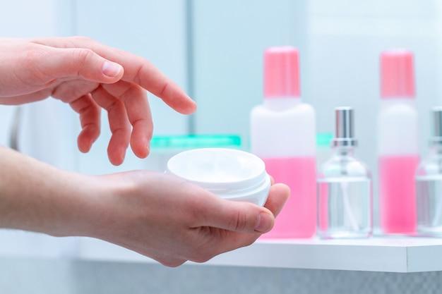 自宅の浴室で乾燥肌にクリームジャーを使用する。保湿と栄養のボディクリームを適用します。皮膚栄養