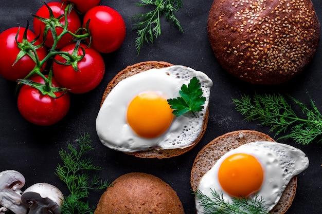健康的な朝食のためのディル、パセリ、トマト、ゴマパンと自家製の新鮮な揚げ鶏の卵。上面図。タンパク質食品。卵サンドイッチ
