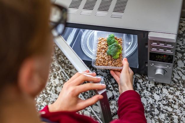 電子レンジを使用して食品を加熱します。女性の手は、ブロッコリーとそばのプラスチック容器を電子レンジに入れます