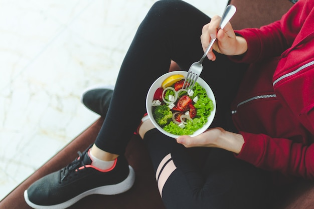 スニーカーとスポーツウェアのフィットネス女性は休憩し、トレーニング後に健康的な新鮮なサラダを食べています。健康的なライフスタイルのコンセプト。