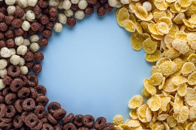 乾燥、チョコレートボール、リング、健康的なシリアルの朝食フレームの背景の黄色いコーンフレークのミックス