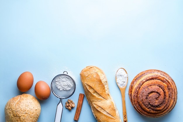 ベーカリー製品のベーキング成分。新鮮なぱりっとしたパン、バゲット、青色の背景にパン。