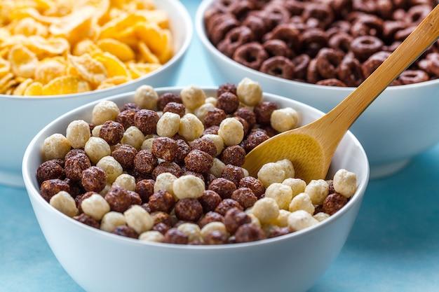 乾燥したシリアル朝食。チョコレートと白と茶色のボールのスプーンとボウル