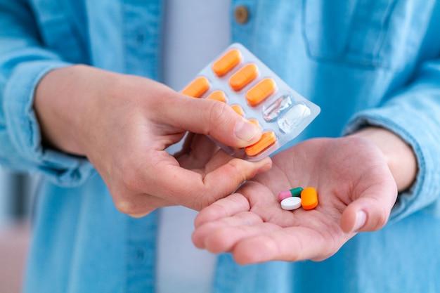 自宅で健康のために薬とビタミンを服用している薬の女性。ヘルスケアおよび治療疾患。
