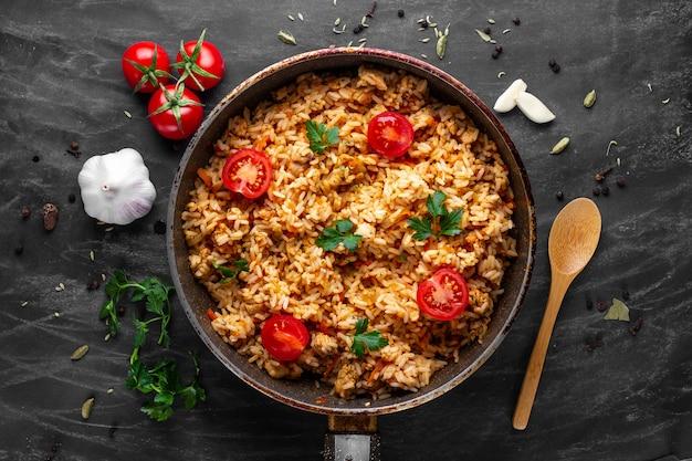 Домашний вкусный плов с курицей, свежей петрушкой и спелыми овощами на сковороде на обед