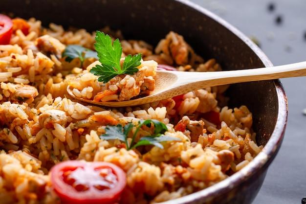 Полная кастрюля домашнего вкусного плова с курицей, свежей петрушкой и спелыми овощами