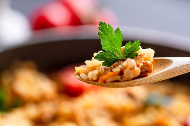 Домашний вкусный плов с курицей, свежей петрушкой и спелыми овощами в деревянной ложке крупным планом