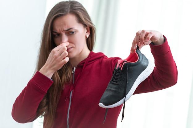女性は長いスポーツトレーニングとアクティブなライフスタイルの後、汗をかいたランニングシューズから不快な臭いを感じています。靴はクリーニングと臭気除去に必要です。靴の手入れと輝き