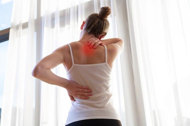 首の痛みと背中の痛みに苦しんでいる若い女性、自宅で筋肉を伸ばします。背中と首の痛みの女性