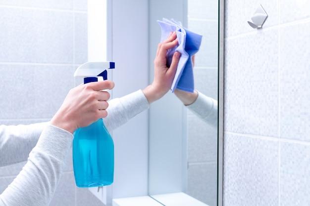 自宅の浴室でぼろとスプレーで鏡を掃除して磨きます。ハウスキーピングとクリーニングサービス。きれいな家、清潔さ