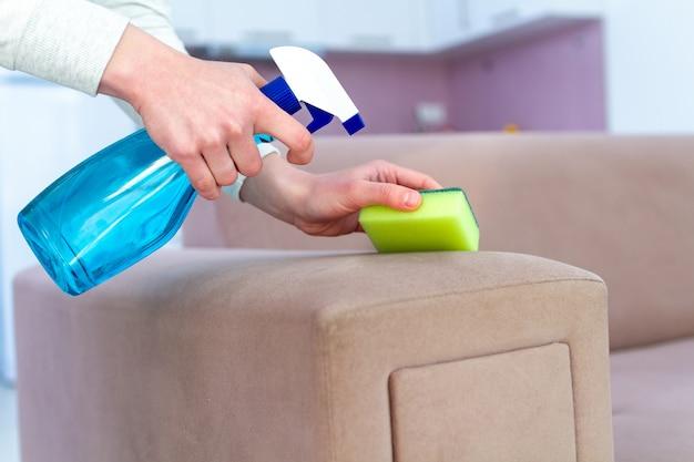 Чистящий диван с губкой и спреем в комнате дома