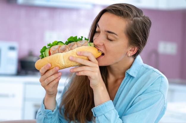 Голодная женщина ест домашний бутерброд. обжорство и лишний вес из-за вредного фаст-фуда и нездорового питания