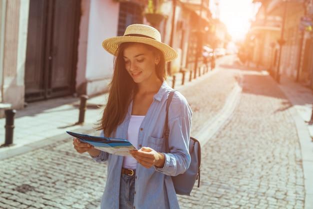 Путешествие женщина в шляпе с рюкзаком, поиск правильного направления на карте путешествий на улице во время путешествия по европе. отпуск и путешествия образ жизни