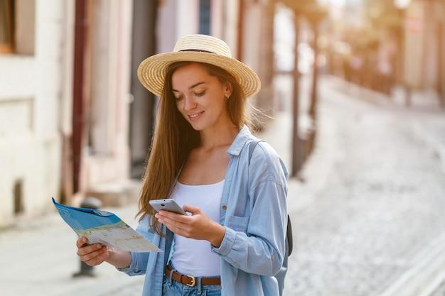 Путешественник женщина в шляпе, поиск правильного направления на карте путешествия во время путешествия по европе. отпуск и путешествия образ жизни