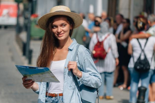 Женщина путешественника в шляпе ища правильное направление на карте перемещения среди толпы туристов пока путешествующ по европе. отпуск и путешествия образ жизни