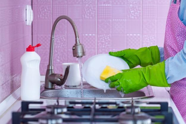 ゴム手袋とエプロンの主婦が自宅でスポンジと洗剤で皿を洗う