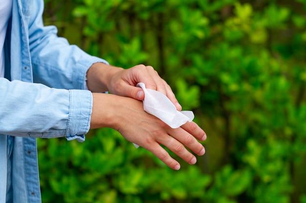 抗菌性のウェットワイプを使用して、公園で手を掃除し、消毒する
