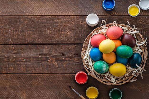 イースター、おめでとう。イースター休暇のための木製の背景にバスケットのカラフルな卵。トップビュー、コピースペース
