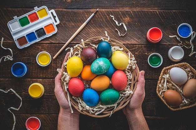 イースター、おめでとう。イースター休暇のためのカラフルな卵の塗装と準備。上面図。木製のテーブルの上の手でバスケットの着色された卵