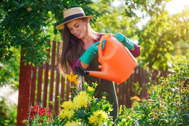 Счастливая женщина садовника в цветках шляпы моча используя чонсервную банку в домашнем саде. садоводство и цветоводство, уход за цветами