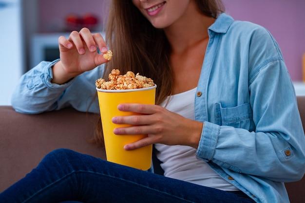 Счастливая молодая женщина улыбки отдыхая и есть хрустящий попкорн карамельки во время смотреть тв дома. попкорн фильм