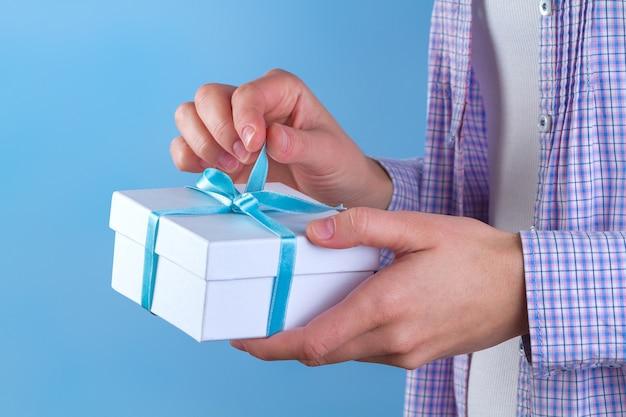 Женские руки открывают подарочную коробку.