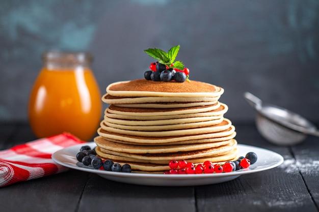 おいしい朝食用の新鮮なベリーと蜂蜜の瓶と自家製のおいしいパンケーキの山